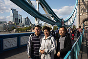 Chinese tourists posing to have their photo taken at Tower Bridge in London, England, United Kingdom. Scenes of both tourists and local office workers enjoying hanging out on the grass at the London Bridge City Park near to Tower Bridge. This area is an icon for tourism, bringing thousands of people in each day.