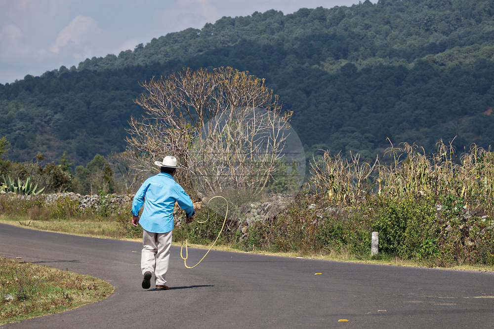 A Mexican cowboy walks down a rural road practicing his lasso skills outside Cucuchucho, Michoacan, Mexico.