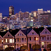 Painted Lady Victorian houses in foreground, downtown San Francisco skyline illuminated in background at dusk, view from Alamo Square Park.