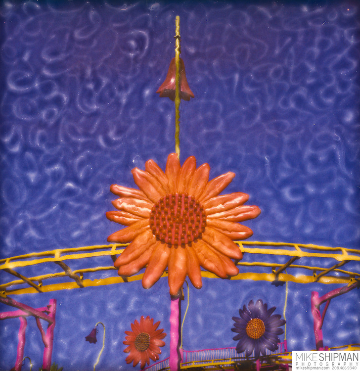 A colorful kiddie ride, a miniature roller coaster, is festooned with large plastic flowers