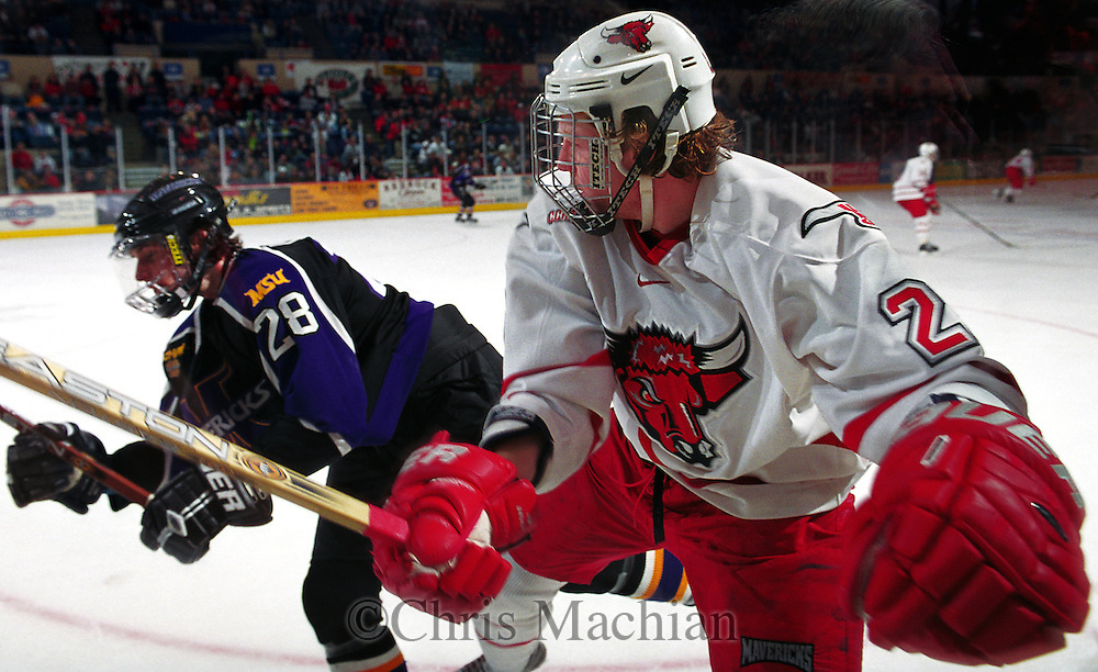 Mankato's Nate Metcalf gets a parting shot on University of Nebraska at Omaha's Mike Lefley into the boards.<br /> (photo by Chris Machian/Prairie PIxel Group)