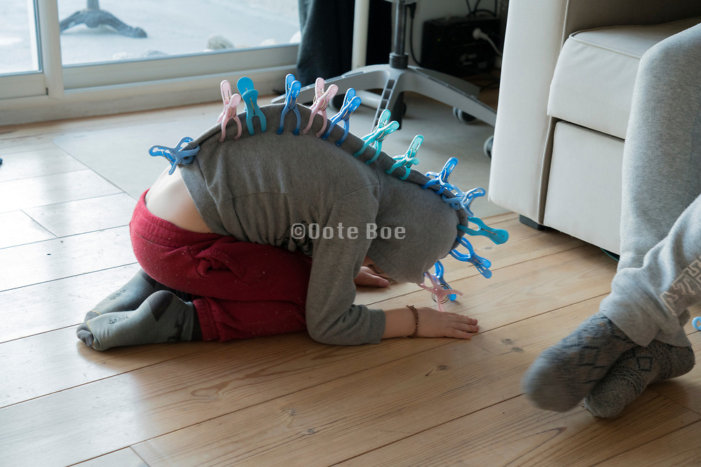 young boy using plastic clothing clips to play a prehistoric animal