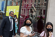 On the day that covid pandemic guidelines for shoppers in England mean that the wearing of face coverings in shops becomes mandatory, shoppers wearing face masks pass Harvey Nichols in Knightsbridge, on 24th July 2020, in London, England.