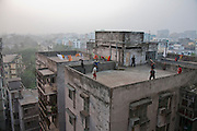 Young men play cricket and soccer on the roof of a building next to the Ananta Clothing Factory on Elephant Road.