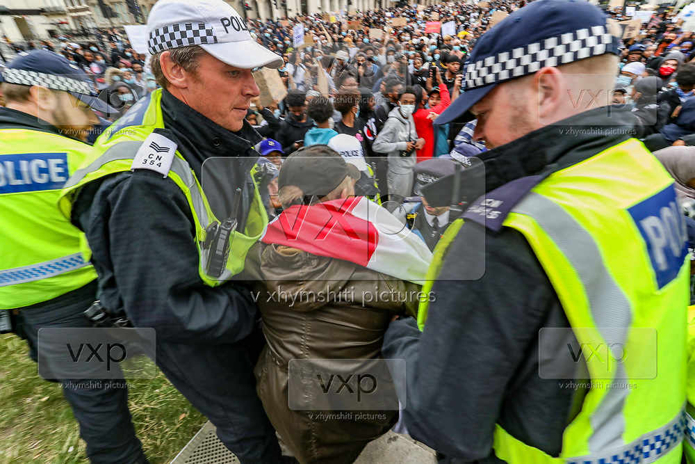 """Police lead away a counter protestor at a Justice for Shukri Abdi rally in Parliament Square, London, following a raft of Black Lives Matter protests across the UK. People take part in a """"Justice for Shukri Abdi"""" protest on the first anniversary of her death, Saturday, June 27, 2020, in London.<br /> The 12-year-old schoolgirl of Somali heritage, who was born in a refugee camp in Kenya, drowned in the River Irwell in Bury, Greater Manchester on June 27, 2019. Greater Manchester Police said it was treating what happened as a """"tragic incident"""" and did not believe there were any suspicious circumstances. Campaigners and the mayor of Greater Manchester are pressing for a full investigation, an inquest was adjourned in February. (Photo/ Vudi Xhymshiti)"""