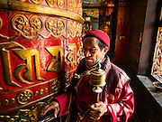 02 MARCH 2017 - KATHMANDU, NEPAL: People pray and spin a prayer wheel in a monastery next to Boudhanath Stupa. The stupa is the holiest site in Nepali Buddhism. It is also the center of the Tibetan exile community in Kathmandu. The Stupa was badly damaged in the 2015 earthquake but was one of the first buildings renovated. PHOTO BY JACK KURTZ