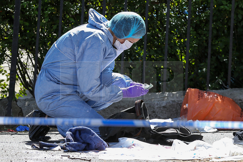© Licensed to London News Pictures. 01/06/2019. London, UK. A forensic officer counting the money found in the victims jacket on Seven Sisters Road, near the junction of Vartry Road in Haringey, north London, where a man in his 30s was found suffering from a stab wound to his leg. Police were called by London Ambulance Service just after 3am on Saturday, 1 June 2019. The victims condition in unknown.  Photo credit: Dinendra Haria/LNP