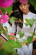 Portrait of a young Vietnamese woman seen through a flowering tree, Khanh Hoa province, Vietnam, Southeast Asia