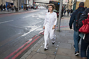 A young woman who works at the London Dungeon tourist attraction at London Bridge walking along Tooley Street while on a break. Her white overalls and face marked with fake blood. London, UK.
