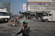 A young woman crosses Tran Hung Dao street, avoiding the traffic in front of the train station in Vinh, Vietnam, Asia