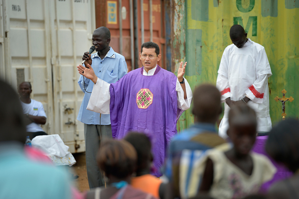 Father Raimundo Rocha celebrates Catholic Mass held in a camp for internally displaced families located inside a United Nations base in Juba, South Sudan. The camp holds Nuer families who took refuge there in December 2013 after a political dispute within the country's ruling party quickly fractured the young nation along ethnic and tribal lines. Father Rocha, a Comboni priest from Brazil, was parish priest in Leer and had to flee into the bush for weeks with his people after armed parties attacked the town. The shipping containers behind the alter are there to provide protection from gunfire directed into the camp.