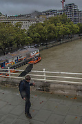 """A man's umbrella is blown by the wind as they walk throughout Waterloo Bridge in London on Friday, Oct 2, 2020. Heavy rain and wind batter capital London, England. Britain is facing gales and heavy downpours as the storm """"Alex"""" is reaching its coasts. (VXP Photo/ Sabrina Merolla)"""