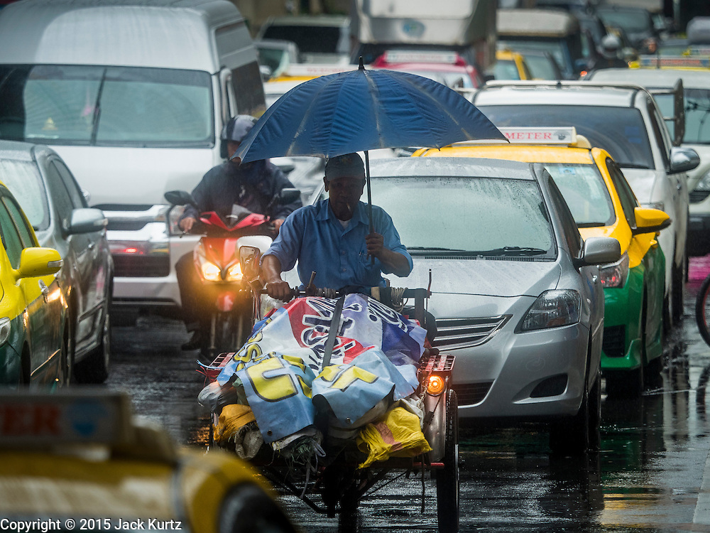 """16 SEPTEMBER 2015 - BANGKOK, THAILAND:  A man under an umbrella rides his motorized trike during a rainstorm in Bangkok. The remnants of tropical storm """"Vamco"""" hit Bangkok Wednesday. The storm, downgraded to a tropical depression, brought bands of rain to central Thailand, including Bangkok. The Thai Meteorological Department said the storm would help alleviate the drought that has gripped Thailand since late last year.    PHOTO BY JACK KURTZ"""