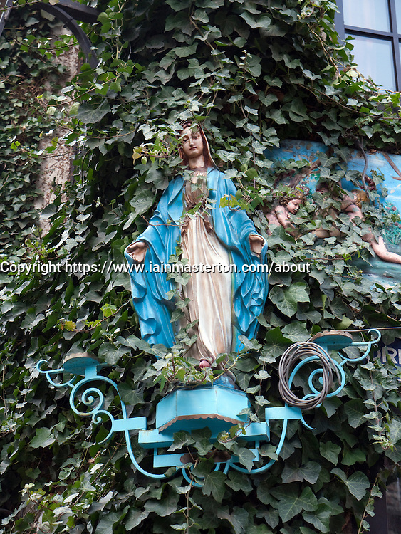 Religious statue covered in ivy on building in old town district of Antwerp Belgium