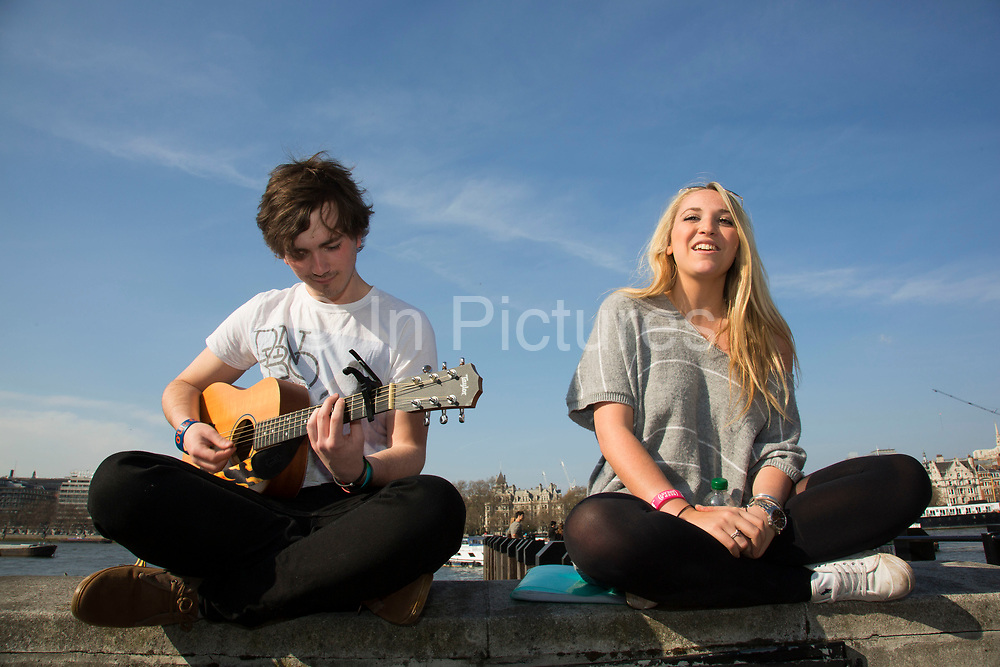Two young buskers singing and playing guitar sitting cross legged on the riverside wall. The South Bank is a significant arts and entertainment district, and home to an endless list of activities for Londoners, visitors and tourists alike.