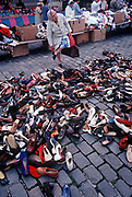 An elderly 1990s lady tries on a left show while standing over a choice of dozens of single items of footwear, in a daily market, on 11th May 1990, in Calais, France.