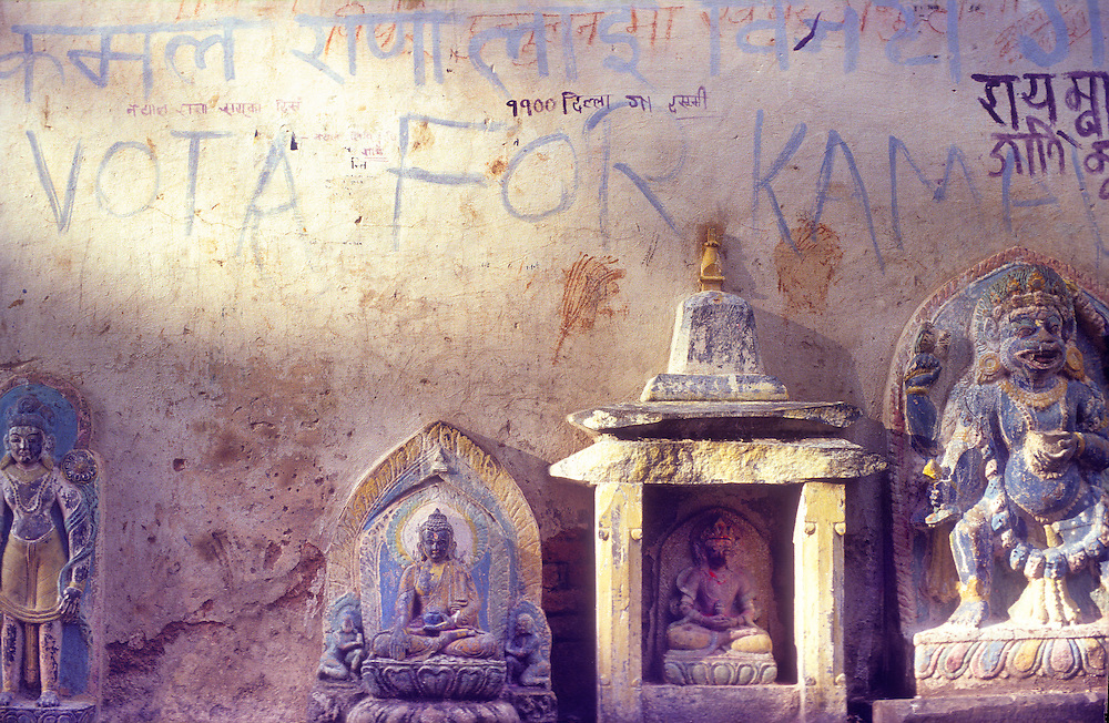 Buddhist and Hindu icons mix with political graffiti on a wall at the Swyambhunath temple complex (also known as The Monkey Temple) on a hill overlooking Nepal's capital city, Kathmandu.