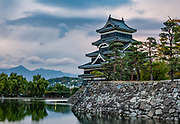 "Matsumoto Castle, built 1592-1614, backed by the Japan Alps in Nagano Prefecture. Matsumoto Castle is a ""hirajiro"" - a castle built on plains rather than on a hill or mountain, in Matsumoto. Matsumotojo's main castle keep and its smaller, second donjon were built from 1592 to 1614, well-fortified as peace was not yet fully achieved at the time. In 1635, when military threats had ceased, a third, barely defended turret and another for moon viewing were added to the castle. Interesting features of the castle include steep wooden stairs, openings to drop stones onto invaders, openings for archers, as well as an observation deck at the top, sixth floor of the main keep with views over the Matsumoto city."