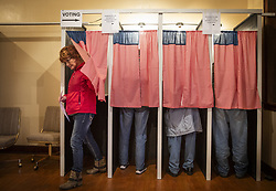 Christine Giroux exits the voting booth at Transit Town Hall Tuesday, November 6, 2018 in Sibley County, Minn. The curtains, an ode the American flag, were sewn by a past election official.Photo by Leila Navidi/Minneapolis Star Tribune/TNS/ABACAPRESS.COM