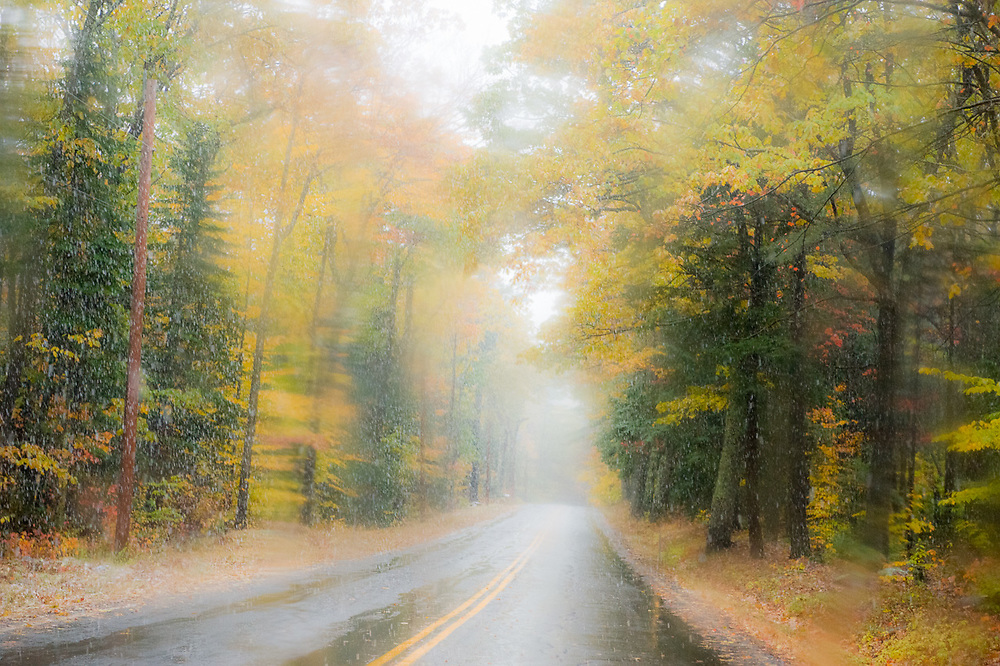 Snowfall along a country road, October, view through a wet windshield, Cheshire County, New Hampshire, USA