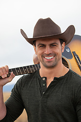 stunning cowboy smiling with his guitar over shoulder
