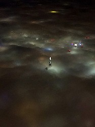 © Licensed to London News Pictures. 01/11/2015. London, UK. A few of fog covering the city of London, taken from a plane by Sarah Wells as she flew in to London early this morning (Sunday). The image shows the Shard building and other London landmarks poking above thick fog and the city lights illuminating the fog.  Photo credit: Sarah Wells/LNP
