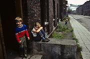 Children play in a desolate street in the town of Nova Huta. Amid the filthy walls of their tenement building home and of the grim, car less street beyond, two older children play in their doorway while younger friends peer from around a corner. It is horribly depressing and unhealthy place to grow up and these children are pale and yet seem happy, with smiles on their faces. The famous steel works can be seen st the end of the street. After the war, Stalin decided to build an ideological communist fantasy just outside Krakow: a model town and immense steelworks of the future. The steelworks was named after Lenin and the town would be called Nova Huta. At its peak, 27,000 people worked at the Lenin Steelworks. But Solidarity grew strong forcing strikes over pay and recognition over their union. Today, it is an economic and ecological disaster area. .