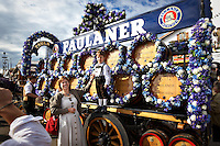 A boy and his mother dressed in German clothes are next to the Paulaner Beer Cart for Oktoberfest in Munich, Germany.