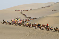 May 1, 2019 - Dunhuang, China - Tourists ride camels in the Crescent Spring and Mingsha Sand Dune scenic area in Dunhuang, northwest China's Gansu Province, the first day of the four-day May Day holiday. (Credit Image: © Xinhua via ZUMA Wire)