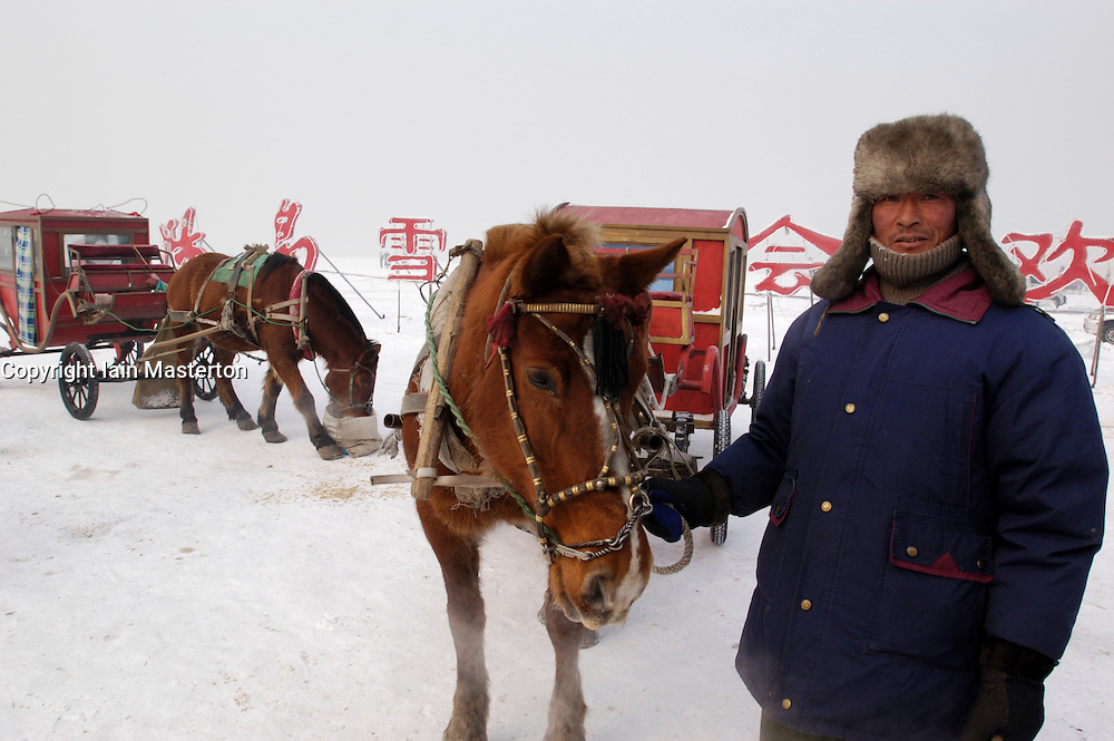 Man with horses and carriages for hire on frozen Songhua River in Harbin China during winter