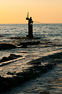 A fisherman sitting on a post and silhouetted by the sea during sunset in Beirut, Lebanon