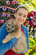 Merrick, New York, USA. 27th May 2013. Liberty the Poodle and her family are by wreaths with red white and blue ribbons and flowers, at the Annual Memorial Day Parade and Ceremony 2013, hosted by American Legion Merrick Post 1282.