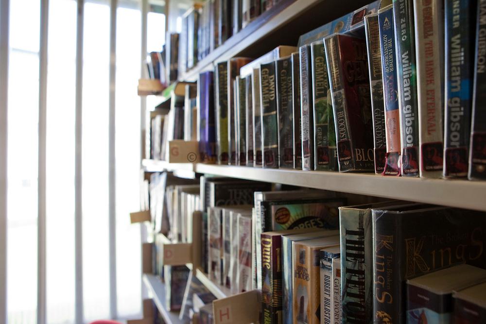 Books on library shelves at HMP Kingston. Portsmouth, United Kingdom. Kingston prison is a category C prison holding indeterminate sentenced prisoners.