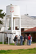 A water tower in the vineyard painted in white and with the winery name on it and a group of visitors. Vinedos y Bodega Filgueira Winery, Cuchilla Verde, Canelones, Montevideo, Uruguay, South America