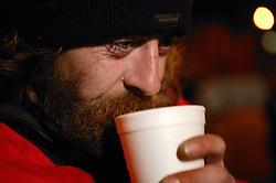 Man enjoying a hot drink from a mobile soup kitchen in Nottingham,