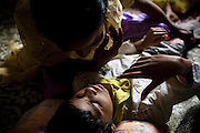 A child is taking part to a physiotherapy session at Chingari Trust while his mother is holding his legs to the ground, talking and reassuring her boy, in Bhopal, Madhya Pradesh. The trust offers assistance, education, physiotherapy and advice to hundreds of children born from gas-affected parents or being fed highly contaminated water since a very early age, when the body is more likely to be affected and to suffer irreparable damage.