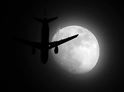 File photo dated 09/03/17 of a plane flying past a Waxing Gibbous moon. Noise from night flights at Heathrow, Gatwick and Stansted will be cut in a new crackdown, Transport Secretary Chris Grayling has said.