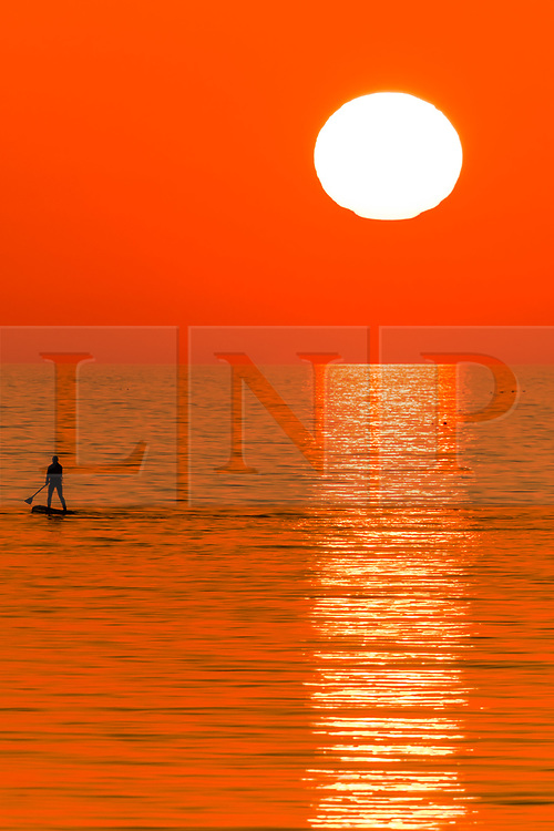 © Licensed to London News Pictures. 27/03/2019. Aberystwyth, UK. Sunset at the end of another day of warm spring sunshine, silhouettes a person paddle-boarding on the flat calm sea at Aberystwyth, on the Cardigan Bay coast of west Wales. High pressure continues to dominate the weather for much of the UK, with settled conditions and clear almost cloudless blue skies. Photo credit: Keith Morris/LNP