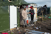 France , Calais, camp for refugees known as 'The Jungle'. November 2015. Two young Eritrean women look at the destruction caused by a fire.