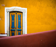 Blue and Yellow Door in Guanajuato, Mexico<br /> ------<br /> Guanajuato is a city and municipality in central Mexico and the capital of the state of the same name. It is part of the macroregion of Bajío. It is in a narrow valley, which makes its streets narrow and winding. Most are alleys that cars cannot pass through, and some are long sets of stairs up the mountainsides. Many of the city's thoroughfares are partially or fully underground. The historic center has numerous small plazas and colonial-era mansions, churches and civil constructions built using pink or green sandstone.<br /> <br /> The origin and growth of Guanajuato resulted from the discovery of minerals in the mountains surrounding it. The mines were so rich that the city was one of the most influential during the colonial period. One of the mines, La Valenciana, accounted for two-thirds of the world's silver production at the height of its production.<br /> <br /> The city is home to the Mummy Museum, which contains naturally mummified bodies that were found in the municipal cemetery between the mid 19th and 20th centuries. It is also home to the Festival Internacional Cervantino, which invites artists and performers from all over the world as well as Mexico. Guanajuato was the site of the first battle of the Mexican War of Independence between insurgent and royalist troops at the Alhóndiga de Granaditas. The city was named a World Heritage Site in 1988.