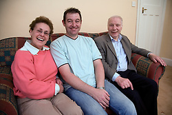 Older couple with their son sitting on the sofa,