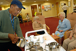 A Care Assistant serves tea to elderly people  in a multi-cultural day centre; Bradford,