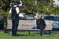 © Licensed to London News Pictures. 15/04/2020. London, UK. A police officer asks a man sitting down to move in Primrose Hill, North London, during a pandemic outbreak of the Coronavirus COVID-19 disease. The public have been told they can only leave their homes when absolutely essential, in an attempt to fight the spread of coronavirus COVID-19 disease. Photo credit: Ben Cawthra/LNP