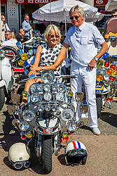 """© Licensed to London News Pictures. 30/08/2020. Brighton, UK. Vespa enthusiasts take to Brighton seafront at the yearly meet. The event takes place every August bank Holiday weekend and celebrates the """"mods and Rockers"""" scene of the sixties with participants dressing up in authentic outfits. Photo credit: Hugo Michiels/LNP"""