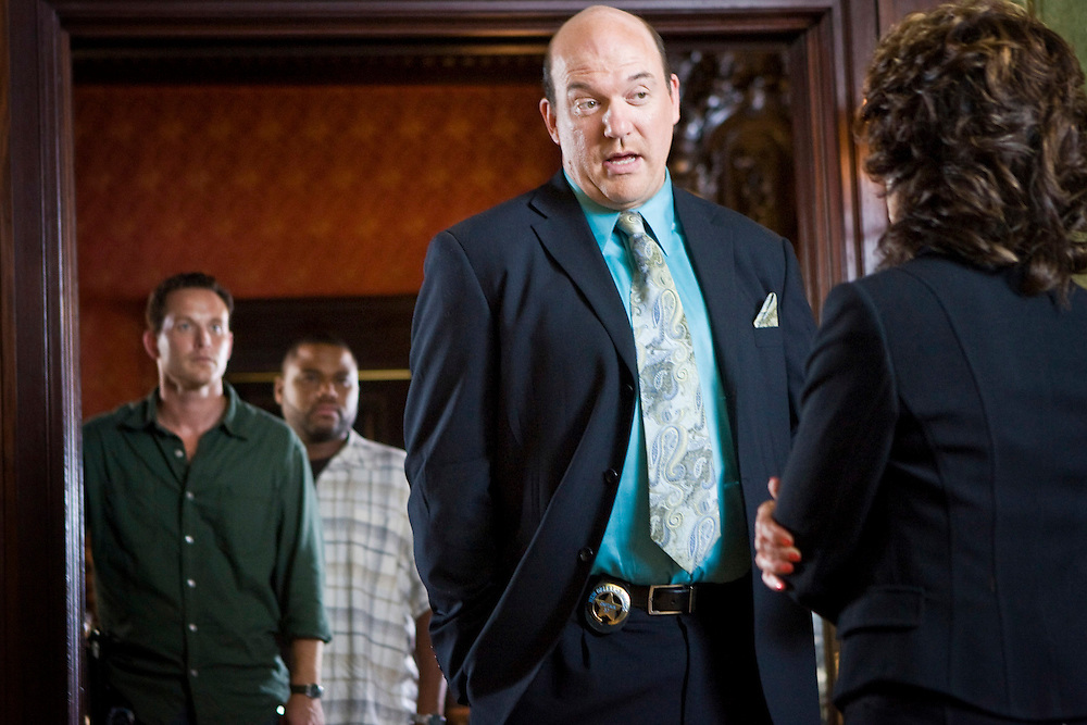 John Carroll Lynch as Captain James Embry speaks to Adrienne Barbeau as Marquetta Dinovi with Cole Hauser as Trevor Cobb and Anthony Anderson as Marlin Boule in the background in Fox Television's 'K-Ville' - a police drama set in New Orleans after Hurricane Katrina.