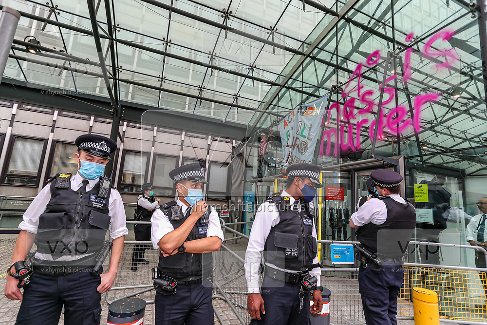 Police rushed to remove photographers and members of the press after a member of Extinction Rebellion sprayed '4 Degree is Mass Murder' in the windows of Department for Business and Energy in Victoria Street, central London on Monday, Sept 7, 2020. The activist also unfurled a banner saying 'ACT NOW FOR ALL OUR CHILDREN' - and glued his hands into the iron bars of the building.<br /> Environmental nonviolent activists group Extinction Rebellion enters its 7th day of continuous ten days protests to disrupt political institutions throughout peaceful actions swarming central London into a standoff, demanding that central government obeys and delivers Climate Emergency bill. (VXP Photo/ Vudi Xhymshiti)