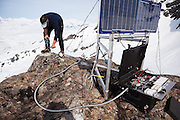 Ian Howat, a glaciologist with Ohio State University, installs an antenna for a GPS base station overlooking the Columbia Glacier, near Valdez, Alaska. The base station communicates with GPS rovers set out on the ice to measure velocities at the glacier surface.