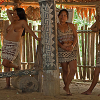Amazon Indians of the Bora tribe near Iquitos, Peru prepare to dance for tourists - perhaps a sideline to more modern workaday jobs.