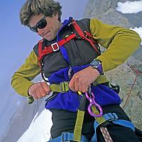 BAFFIN ISLAND, Nunavut, Canada. Alex Lowe (MR) harnesses up at start of Great Sail Peak big wall climbing expedition.