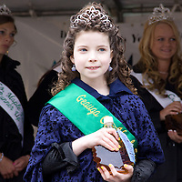 Geauga County Maple Festival Princess Genevieve Baker presents a blue ribbon maple syrup for the crowd to bid on during the festival's maple syrup auction.